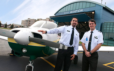 Two student pilots standing by a FSC plane.