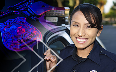 Smiling female police officer standing beside a police car