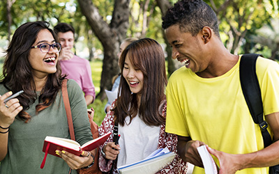 Group of three diverse students laughing walking outside on campus