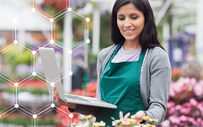 Female horticulture student wearing a green apron holding a laptop in a greenhouse filled with colorful flowers and plants.