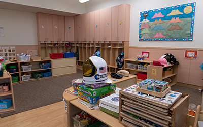 Childcare classroom with wood cabinets and cubbies.