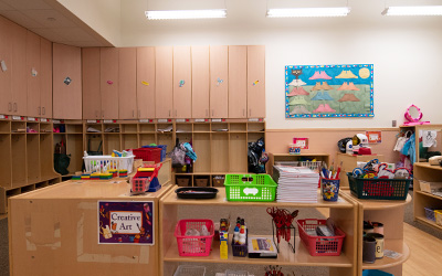 Childcare center classroom with wood cubbies, colorful art on the walls, books and educational toys on shelves.