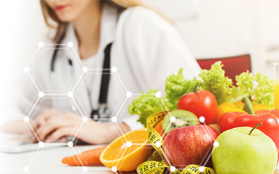 Female nutrition student taking notes with fresh fruits and vegetables on the table beside her.