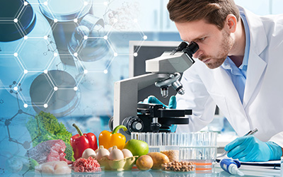 Male student in white labcoat looking in a microscope with fresh vegetables and fruits on the table near him.