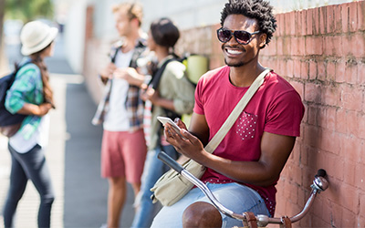 Male college student smiling leaning against a wall with other students in the background.