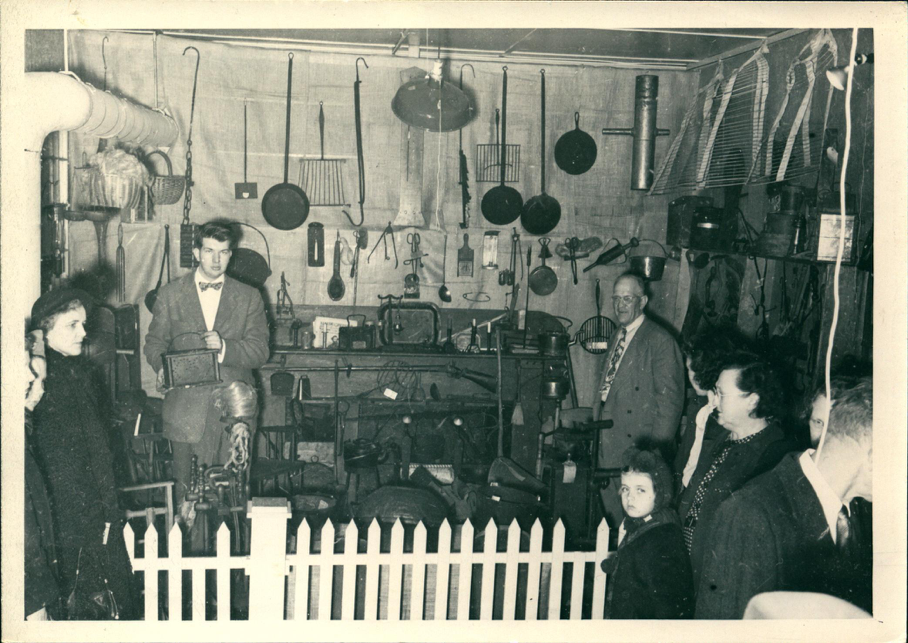 Mr. George Simmons, former Institute faculty, with part of his collection of antique artifacts (Mr. Simmons at right in the grey suit – a student assistant, and visitors). He exhibited at Country Life Programs several years in the 1940s-1950s.