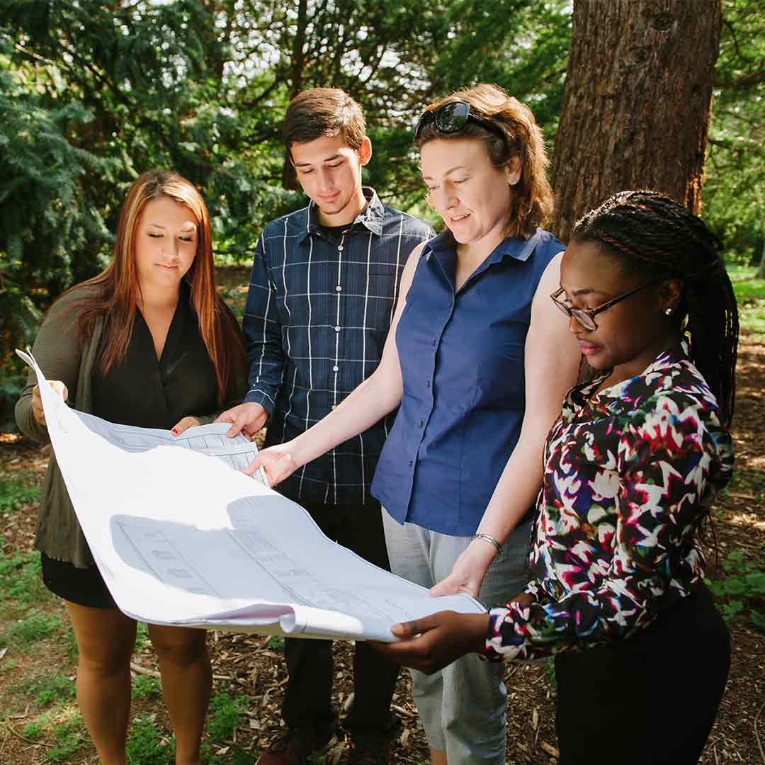 Professor Orla LoPiccolo and students reviewing blueprints