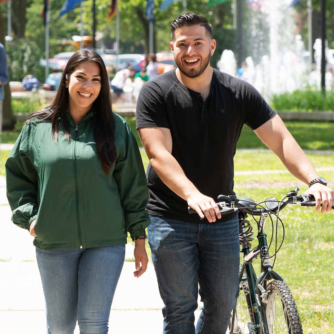 Two students walking with bicycle.