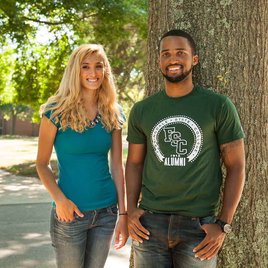 Two smiling students by a tree.