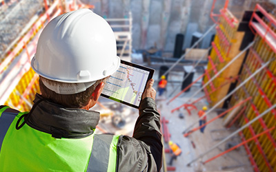 Inspector in hard hat on building site viewing energy results on a computer tablet.