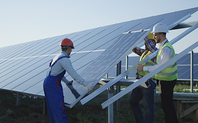Three men wearing hard hats installing solar panels.