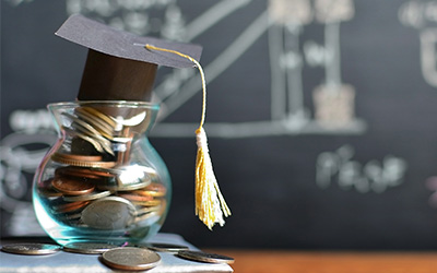 Jar of coins topped with graduation cap in front of a black board