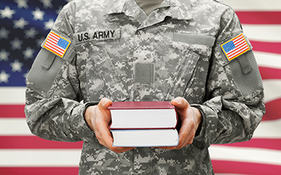 US Army military member in uniform holding textbooks standing in front of an American Flag